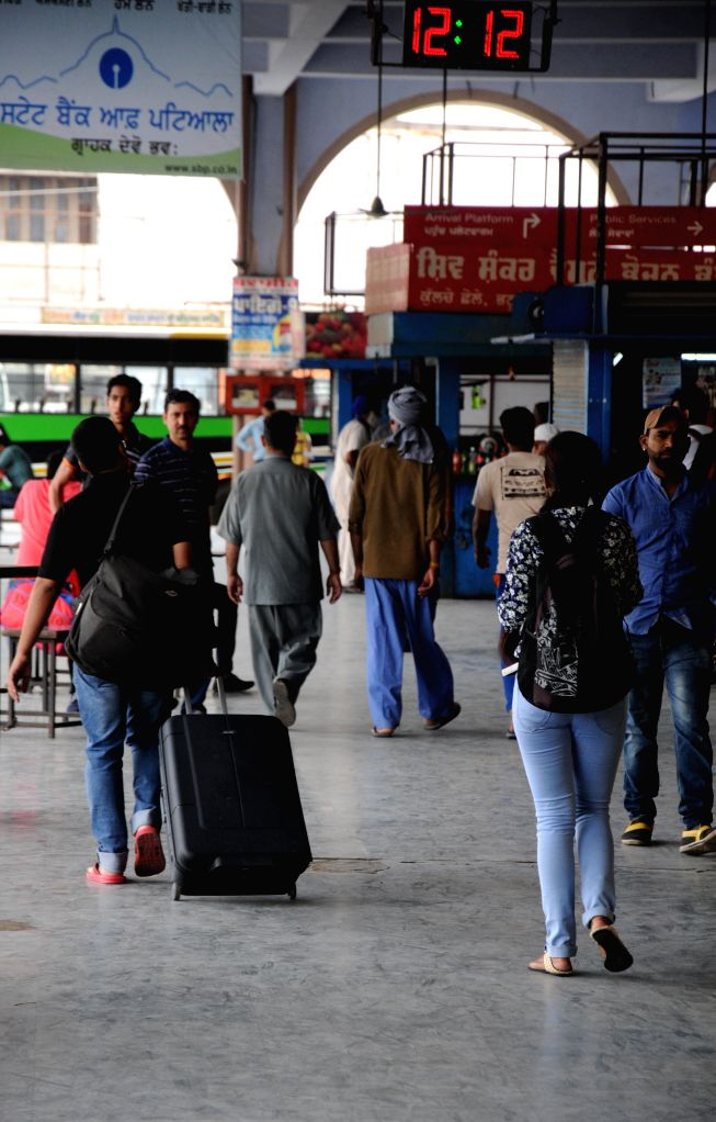 Passengers with their luggage waiting for transport outside at Amritsar Bus terminal due to transport operators go on nation wide strike in Amritsar on April 30, 2015.