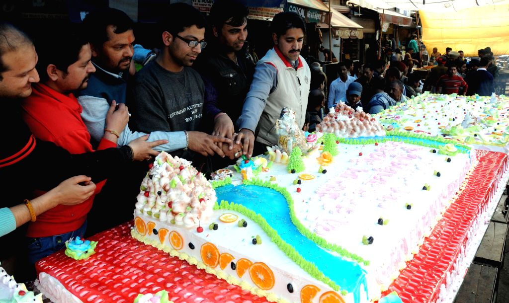 People cut a large cake on Mahashivratri in Amritsar on Feb 17, 2015.