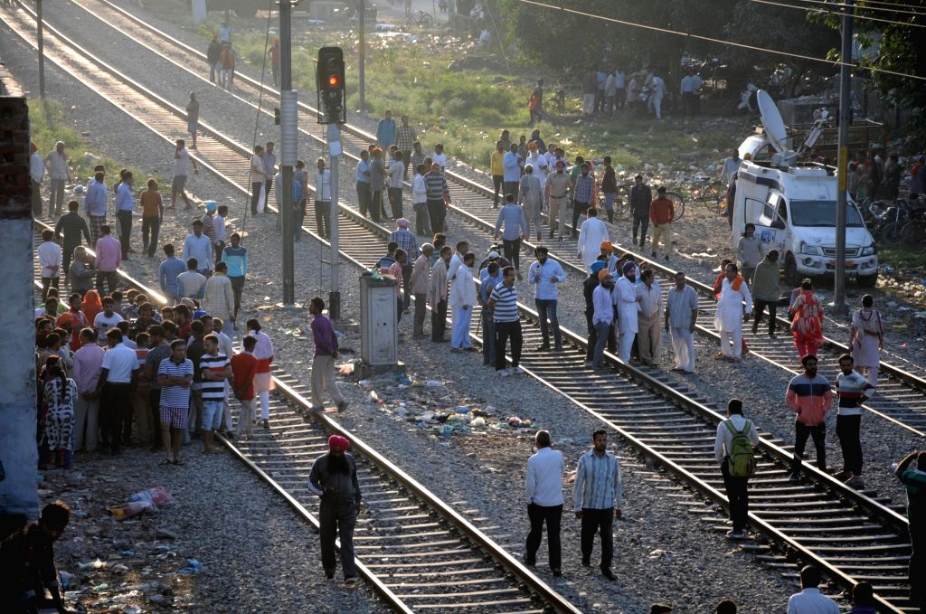 :Amritsar: People gather at the site where a local train crushed at least 58 people and left 72 injured while watching the burning of a Ravana effigy from a railway track last night; in Amritsar on ...