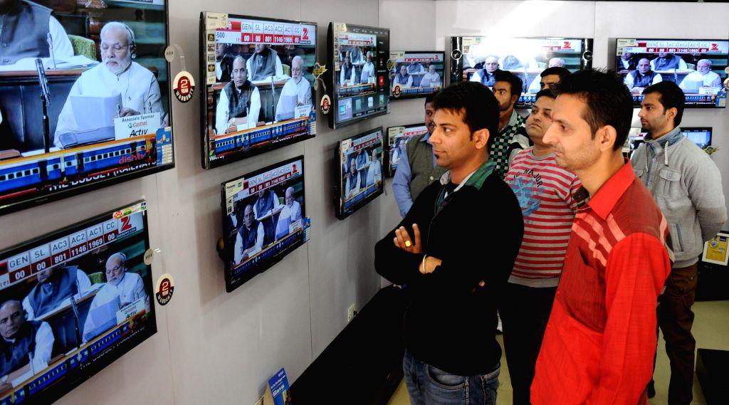 People glued to the television screens as Union Railways Minister Suresh Prabhakar Prabhu presents Railway Budget 2015-16 at the Parliament, in Amritsar, on Feb 26, 2015. - Suresh Prabhakar Prabhu