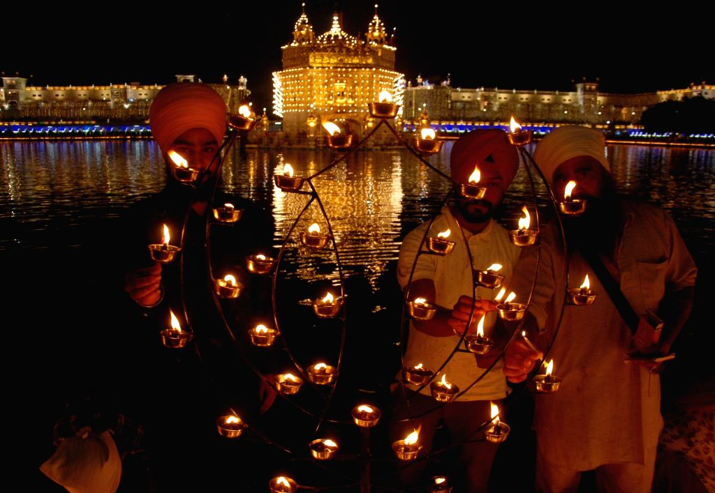 Amritsar: People light earthen lamps during Diwali celebrations, at Golden Temple in Amritsar on Oct 27, 2019. (Photo: IANS)