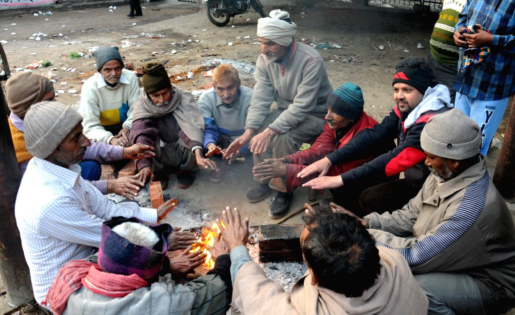 People warm themselves around a fire in Amritsar, on Dec 25, 2014.