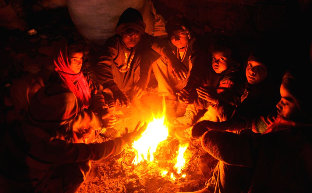 People warm themselves around a fire in Amritsar, on Dec 29, 2014.