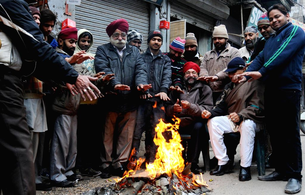 People warm themselves around a fire in Amritsar on Jan. 10, 2014.