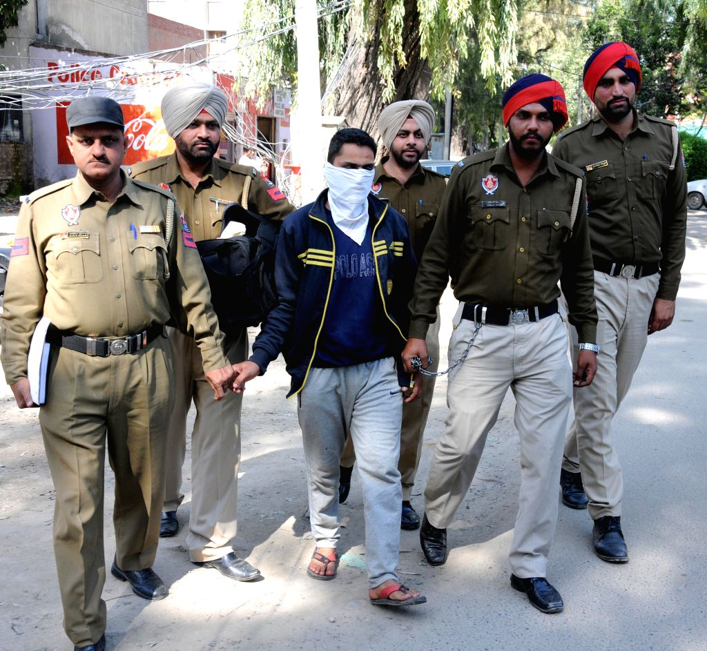 Policemen present before press the smugglers arrested with 3 kg heroin - worth Rs. 15 crores in the international market - in Amritsar on March 10, 2015.