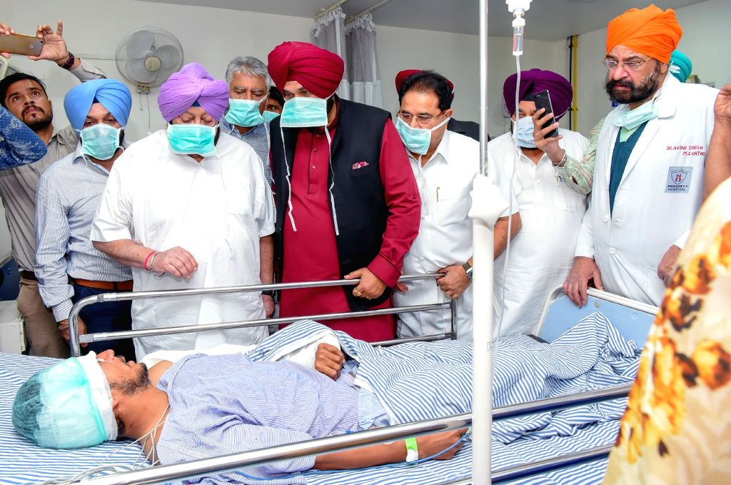 : Amritsar: Punjab Chief Minister Captain Amarinder Singh and state Cabinet Minister Navjot Singh Sidhu meet an accident victim at Civil Hospital after a local train crushed at least 58 people and ...