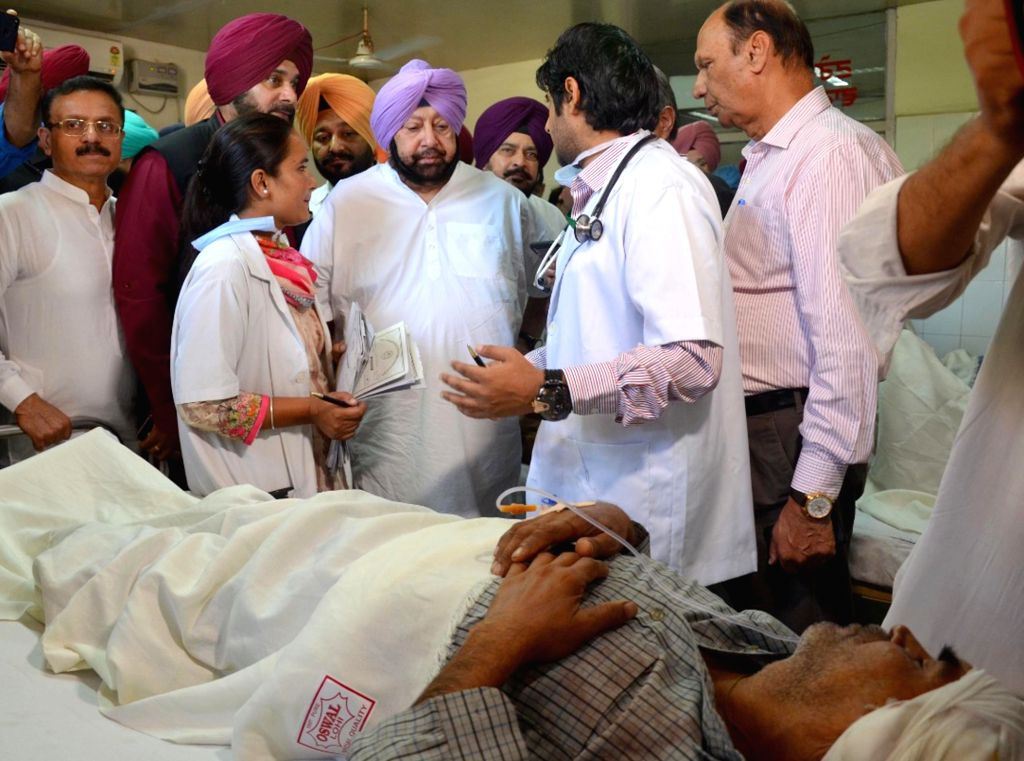 : Amritsar: Punjab Chief Minister Captain Amarinder Singh and state Cabinet Minister Navjot Singh Sidhu meet an accident victim at Civil Hospital after a local train crushed at least 60 people and ...