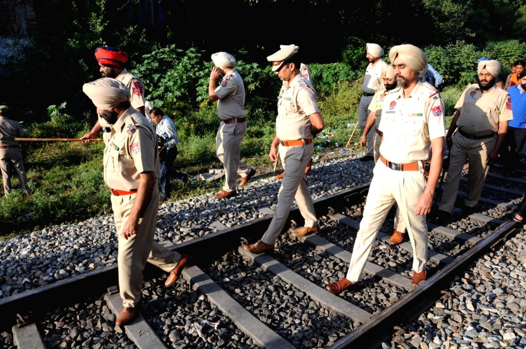 : Amritsar: Punjab police personnel during investigation at the site where a local train crushed at least 58 people and left 72 injured while watching the burning of a Ravana effigy from a railway ...