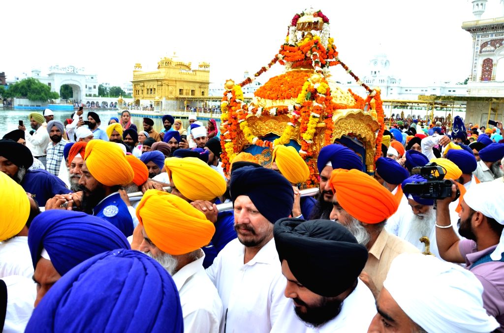 Amritsar: Sikh devotees carry Guru Granth Sahib in a decorated palanquin during 'Nagar Kirtan' (religious procession) that is on its way to the Dera Baba Nanak in Punjab's Gurdaspur district, organised to mark the 550th birth anniversary of Guru Nana - Nanak Dev