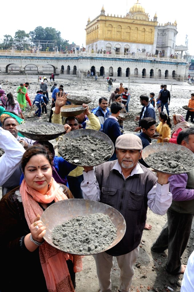 Amritsar: Sikh devotees participate in 'kar sewa' - voluntarily labour -  for cleaning up of the sacred pond at Durgiana Temple, in Amritsar, on March 4, 2019.