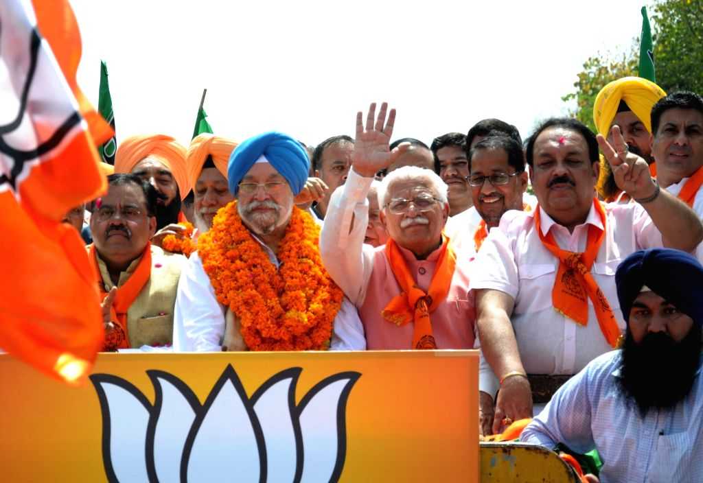 Amritsar: Union Minister and BJP's Lok Sabha candidate from Amritsar,  Hardeep Singh Puri with Haryana Chief Minister Manohar Lal Khattar and BJP leaders Tarun Chugh and Shwait Malik, during a roadshow ahead of filing his nomination for the 2019 Lok  - Manohar Lal Khattar, Malik and Hardeep Singh Puri