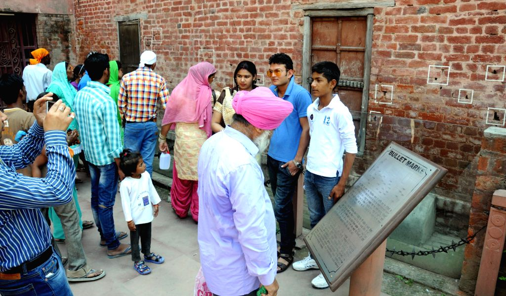 Visitors look on the bullet marks at Jallianwala Bagh on the 96th anniversary of Jallianwala Bagh in which hundreds of freedom fighters were gunned down by British in Amritsar on April 13, ...
