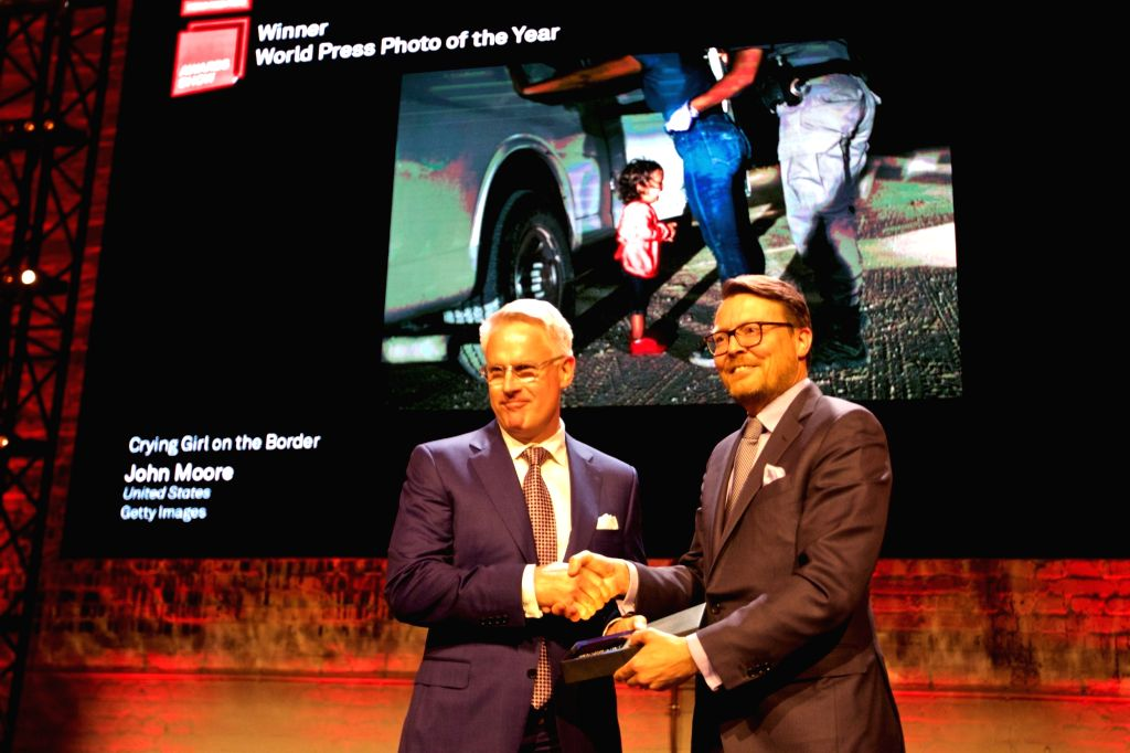 """AMSTERDAM, April 12, 2019 - Dutch Prince Constantijn (R) congratulates John Moore, whose """"Crying Girl on the Border"""" won the hornor of World Press Photo of the Year, in Amsterdam, the ..."""