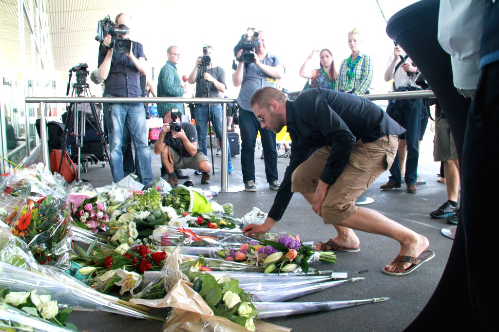 People pay tribute to the people who died after flight MH17 of Malaysia Airlines crashed in east Ukraine, at the Schiphol Airport in Amsterdam, the Netherlands, ..