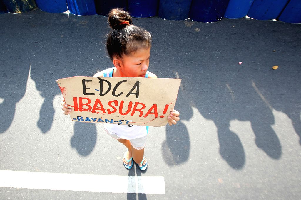 An activist holds a placard during a protest rally in front of the U.S. Embassy in Manila, the Philippines, Jan. 14, 2016. The activists are calling for an end to ...