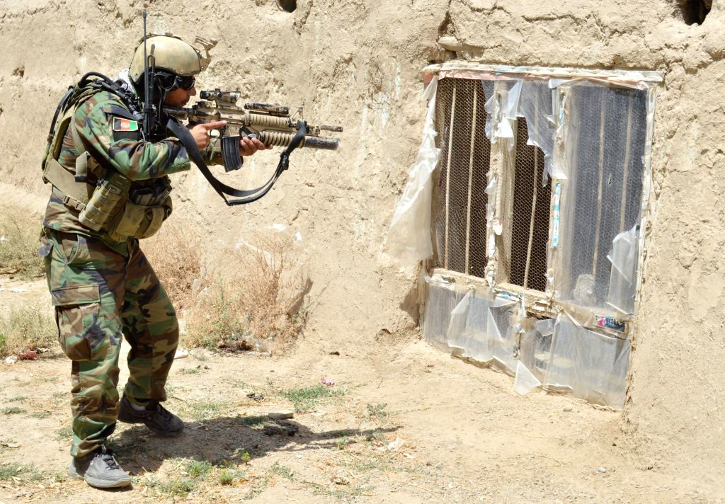 An Afghan army soldier aims his weapon while searching a house during a patrol in Kunduz province, northern Afghanistan, Aug. 9, 2015. Some 36 militants have been ...