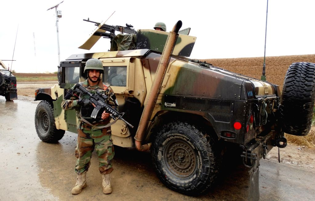 An Afghan army soldier stands guard near a military vehicle in Marjah district of southern Helmand province of Afghanistan, Nov. 14, 2015. Clash between government ... - Mirza Khan Rahimi