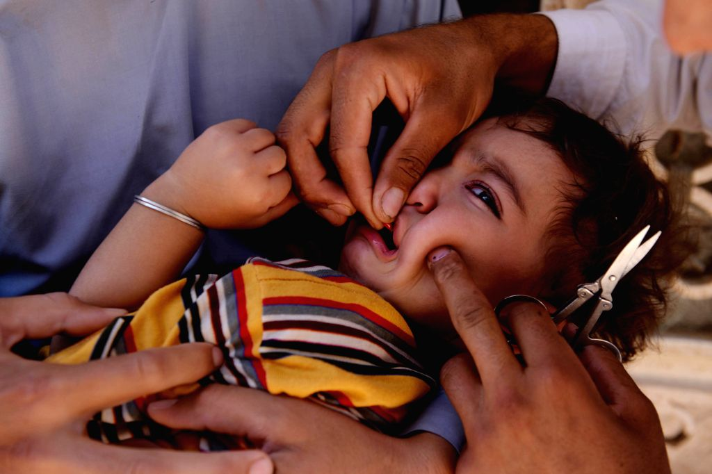 An Afghan health worker administers a polio vaccine to a child during a vaccination campaign in Herat province, western Afghanistan, Aug. 18, 2015. ...