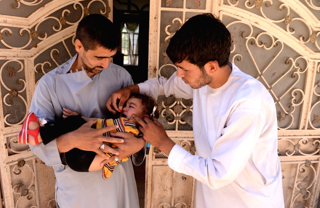 An Afghan health worker administers a polio vaccine to a child during a vaccination campaign in Herat province, western Afghanistan, on Aug. 18, 2015. ...