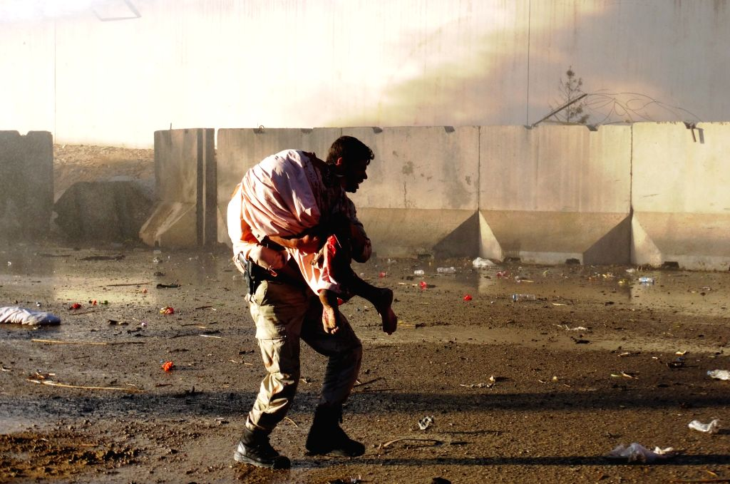 An Afghan man carries an injured man from a blast site in Lashkar Gah, capital of southern Helmand province, Afghanistan, Nov. 15, 2015. At least one police ...