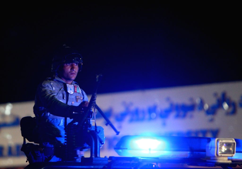 An Afghan policeman stands guard outside the entrance gate of the Afghan police academy following a suicide bombing in Kabul, Afghanistan on Aug. 7, 2015. At least 20 ...