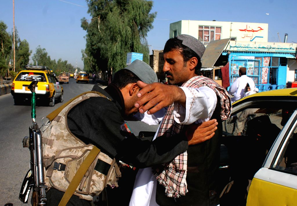 An Afghan soldier does a body search of a passenger at a checkpoint in Kandahar province, southern Afghanistan, on Aug. 18, 2015.
