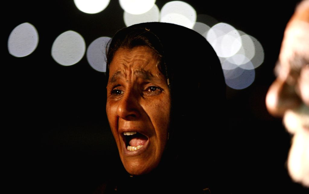 An Afghan woman reacts for her son while standing close to the Afghan police academy following a suicide bombing in Kabul, Afghanistan on Aug. 7, 2015. At least 20 ...