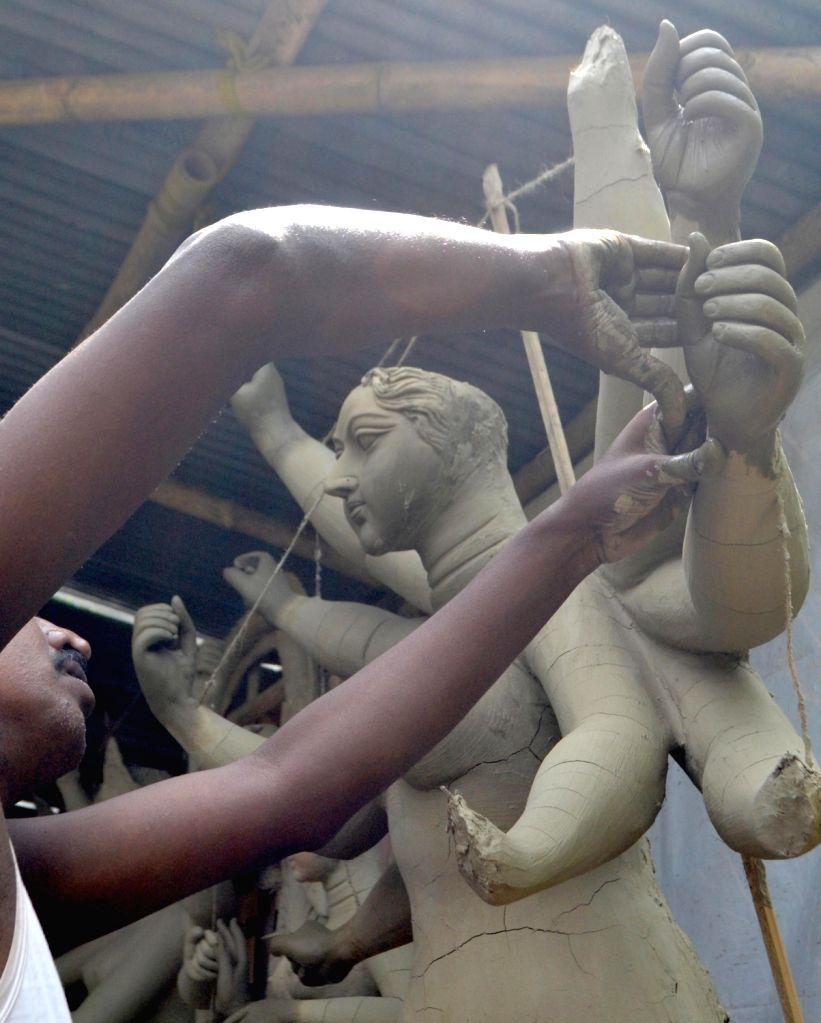 An artisian busy making idol of Goddess Durga ahead of Durga Puja at a workshop in Guwahati on Sept 24, 2016.
