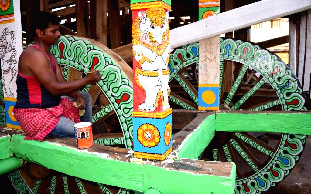 An artist busy giving final touches to the wheels of a wooden chariot ahead of the annual Rath Yatra, in Bhubaneswar on July 9, 2018.