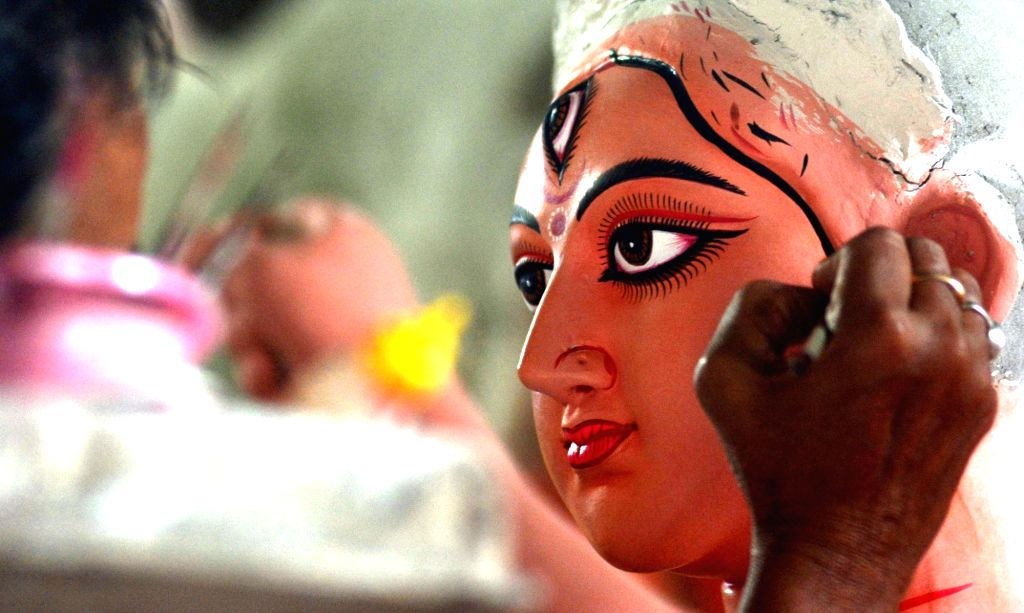 An artist busy giving finishing touches to an idol of Goddess Durga at Kumartuli workshop ahead of Durga Puja celebrations, in Kolkata on Oct 14, 2020.