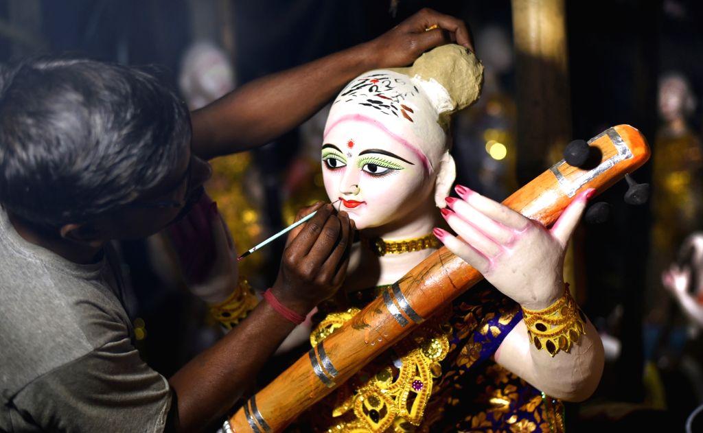 An artist busy giving finishing touches to an idol of goddess Saraswati at a workshop in Bhubandanga, Bolpur on Feb 8, 2019.
