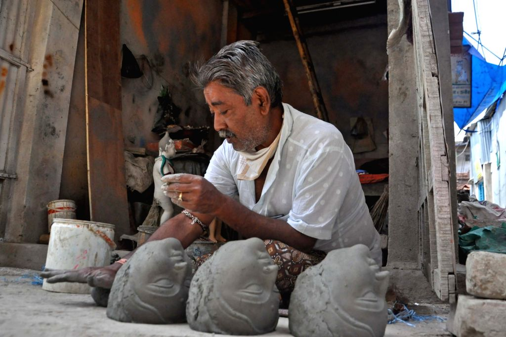 An artist busy making the heads of idols at Kumartully workshop during the 21-day nationwide lockdown imposed to contain the coronavirus, in Kolkata on March 31, 2020.