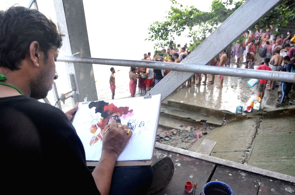 An artist busy painting on the banks of the Ganga river, in Kolkata on Sep 17, 2020.