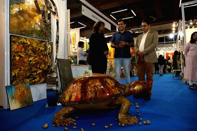An artist explains his artwork as India Art Festival Director Rajendra and chef Sanjeev Kapoor look on at the India Art Festival 2020. - Sanjeev Kapoor