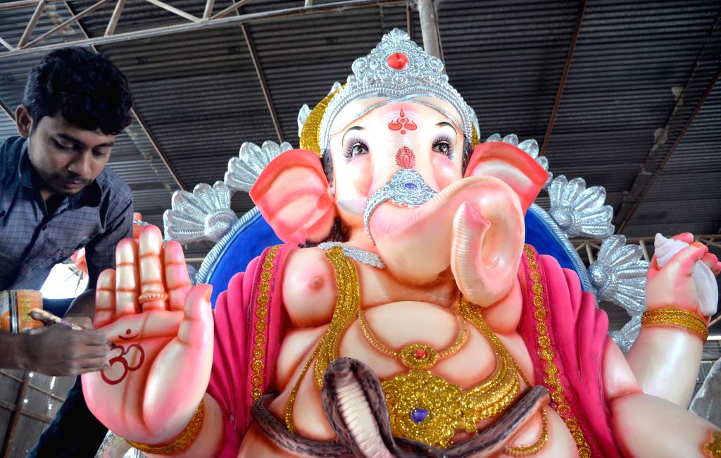 An artist gives final touches to a Ganesh idol at a Bengaluru workshop on Aug 11, 2015.