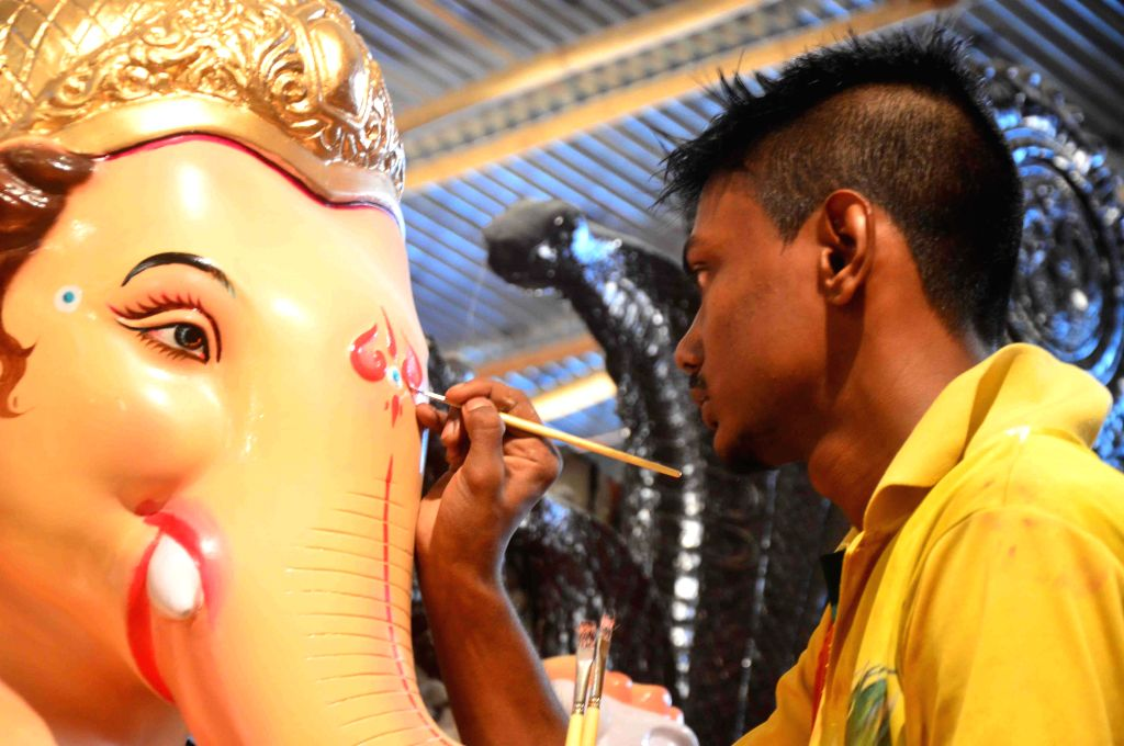 An artist gives final touches to a Ganesh idol at a Mumbai workshop on Aug 16, 2015.