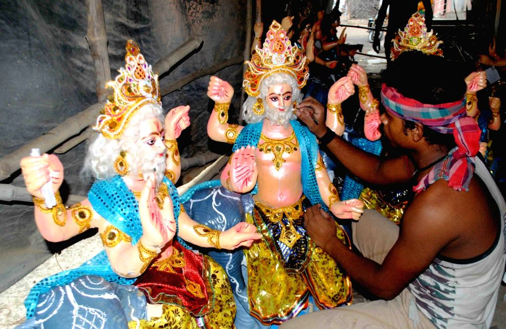 An artist gives final touches to idols of Vishwakarma on the eve of Vishwakarma Puja in Allahabad, on Sept 16, 2016.
