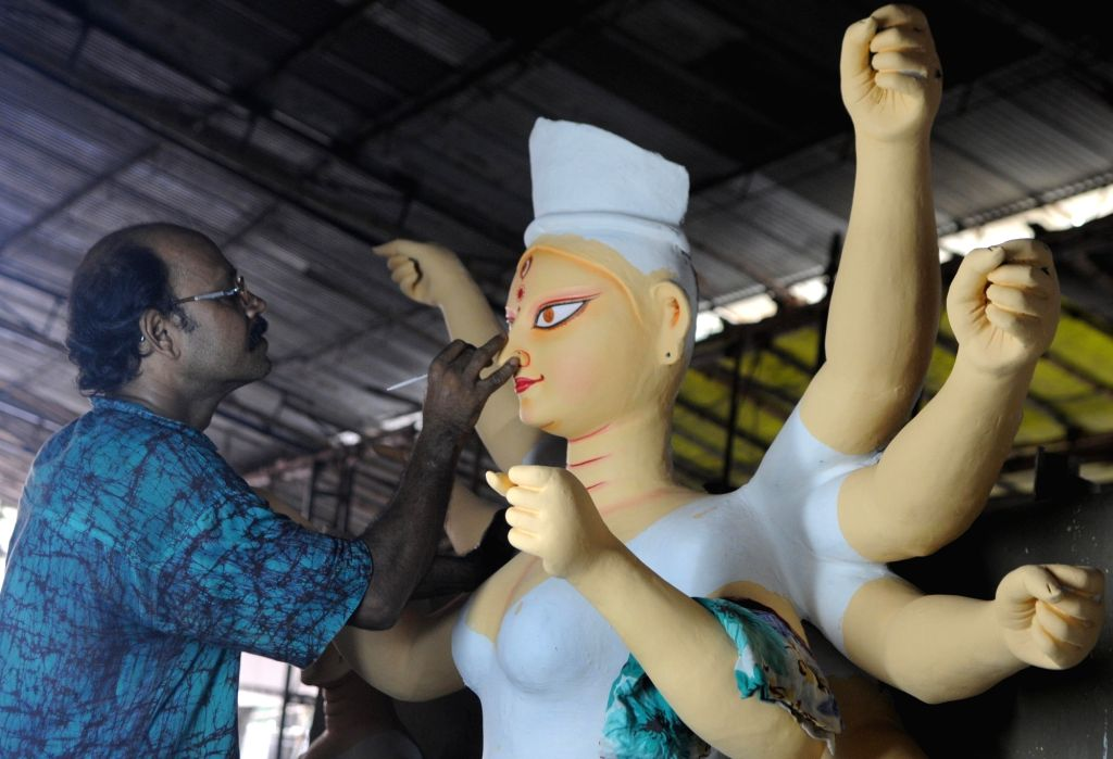 An artist gives finishing touch to an idol of Goddess Durga ahead of Durga Puja at a workshop in New Delhi on Sept 19, 2017.