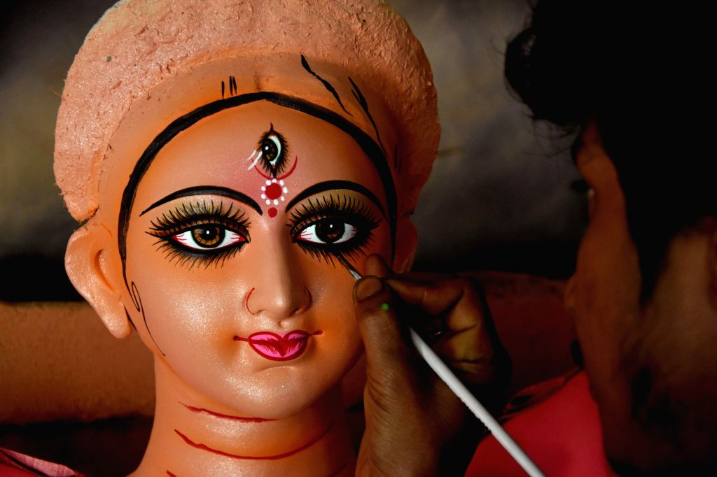 An artist gives finishing touch to an idol of Goddess Durga ahead of Durga Puja in Bengaluru on Sept 20, 2017.