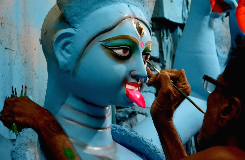 An artist gives finishing touch to an idol of Goddess Kali ahead of Kali Puja in Kolkata on Oct 10, 2017.