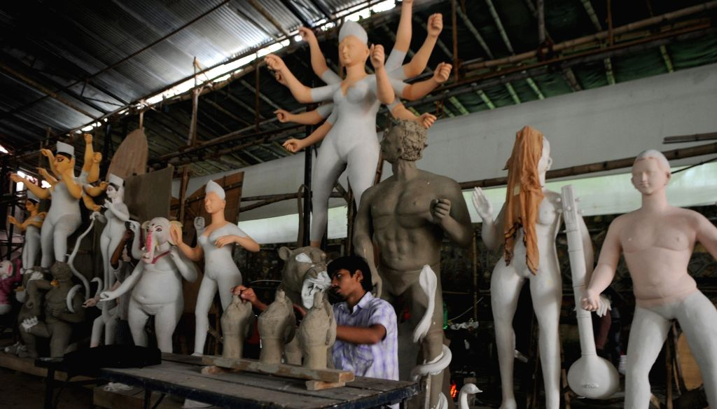 An artist gives finishing touch to the idols at a workshop ahead of Durga Puja in New Delhi on Sept 19, 2017.