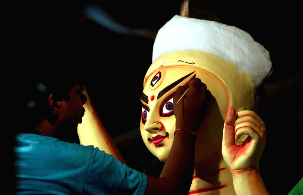 An artist gives finishing touches to a Durga idol at a Delhi workshop on Oct 2, 2016.