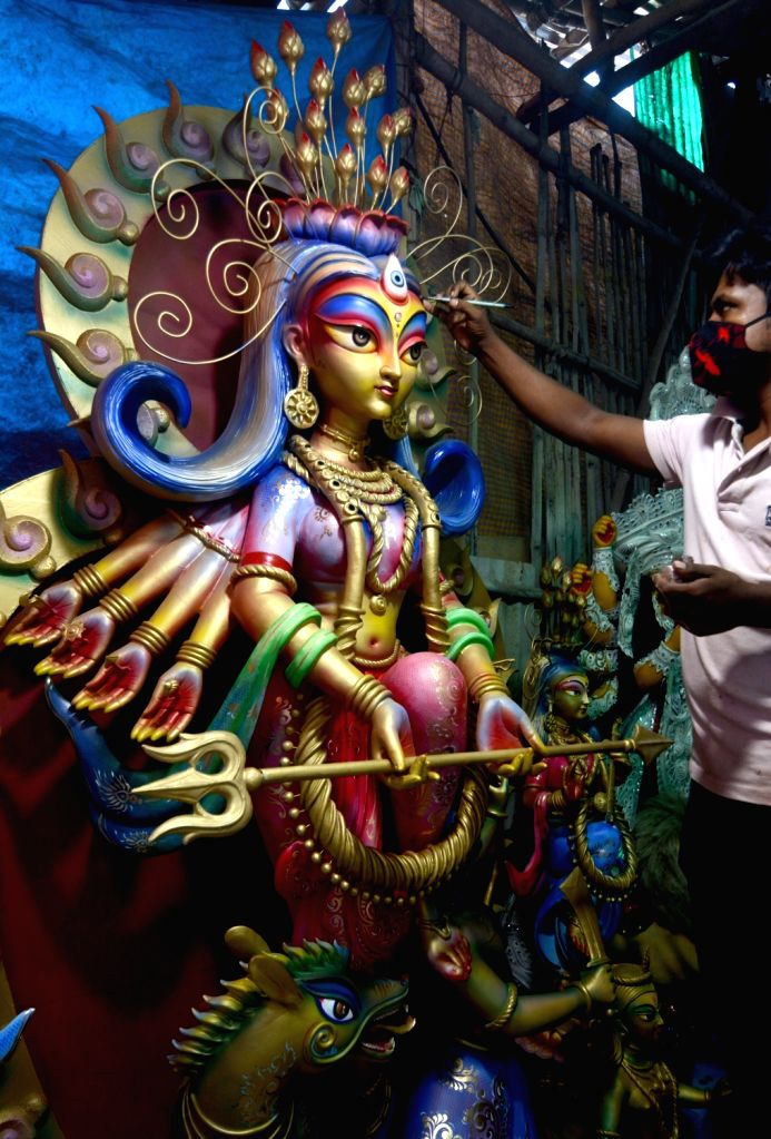 An artist gives finishing touches to an idol of Goddess Durga at the Kumartuli workshop ahead of Durga Puja celebrations, in Kolkata on Oct 15, 2020.