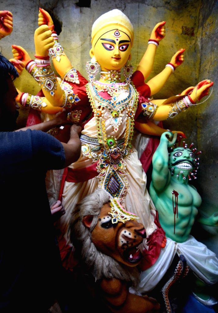 An artist gives finishing touches to an idol of Goddess Durga for a community puja pandal themed on Coronavirus, where the Goddess is seen slaying 'Coronasura' (Monster Corona) instead of ...
