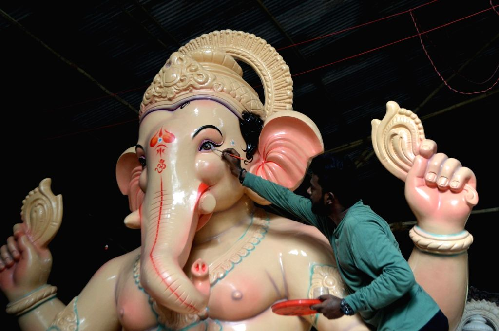 An artist gives finishing touches to an idol of lord Ganesha ahead of Ganesh Chaturthi, at a Mumbai workshop on July 1, 2018.