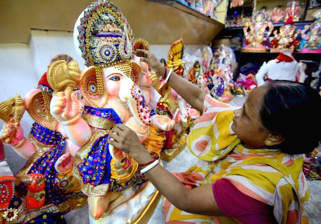 An artist gives finishing touches to an idol of Lord Ganesha ahead of Ganesh Chaturthi celebrations at Kumartuli in Kolkata on Aug 25, 2019.