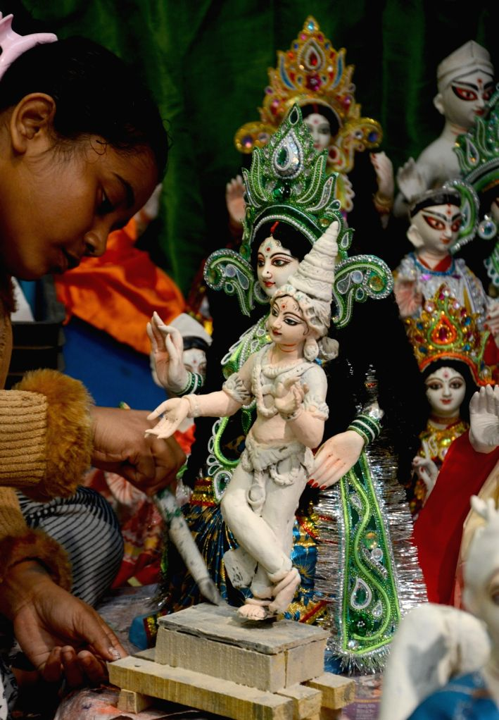 An artist gives finishing touches to an idol of Goddess Saraswati ahead of Saraswati Puja celebrations, at a workshop in Kolkata on Jan 27, 2020.