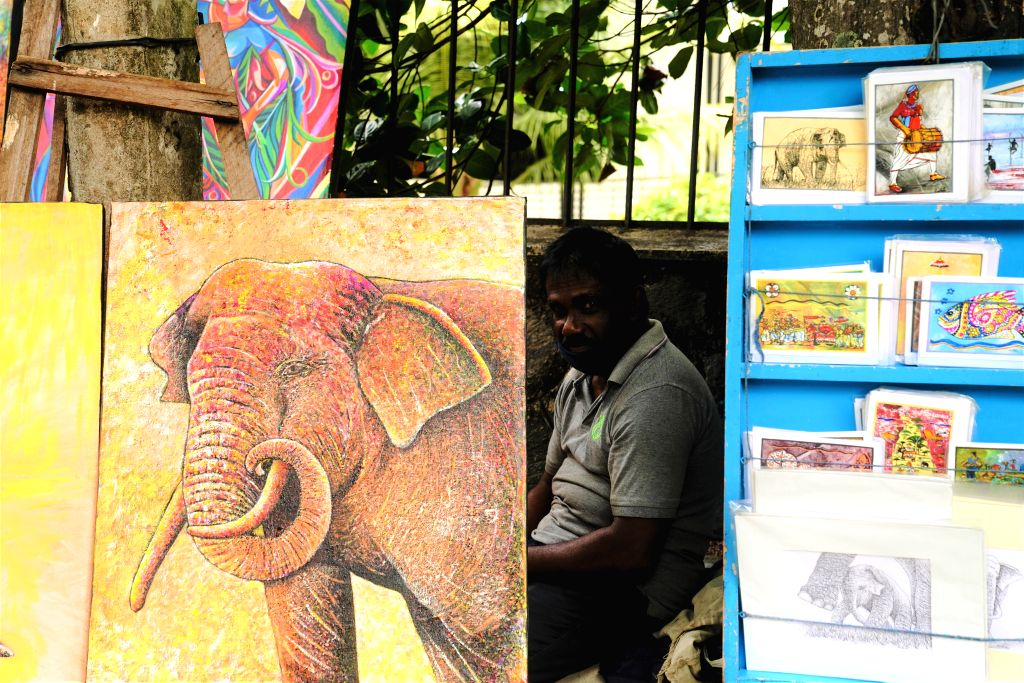 An artist is seen with his artworks at Green Path, a hub of open-air art shows, in Colombo, capital of Sri Lanka, on July 4, 2020. Open-air art shows at Green Path ...