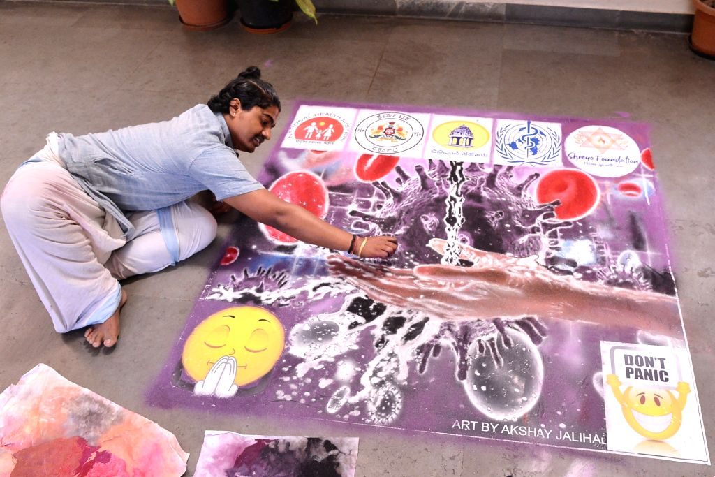 An artist paints a poster to spread awareness on COVID-19 (coronavirus) in Bengaluru on March 18, 2020.