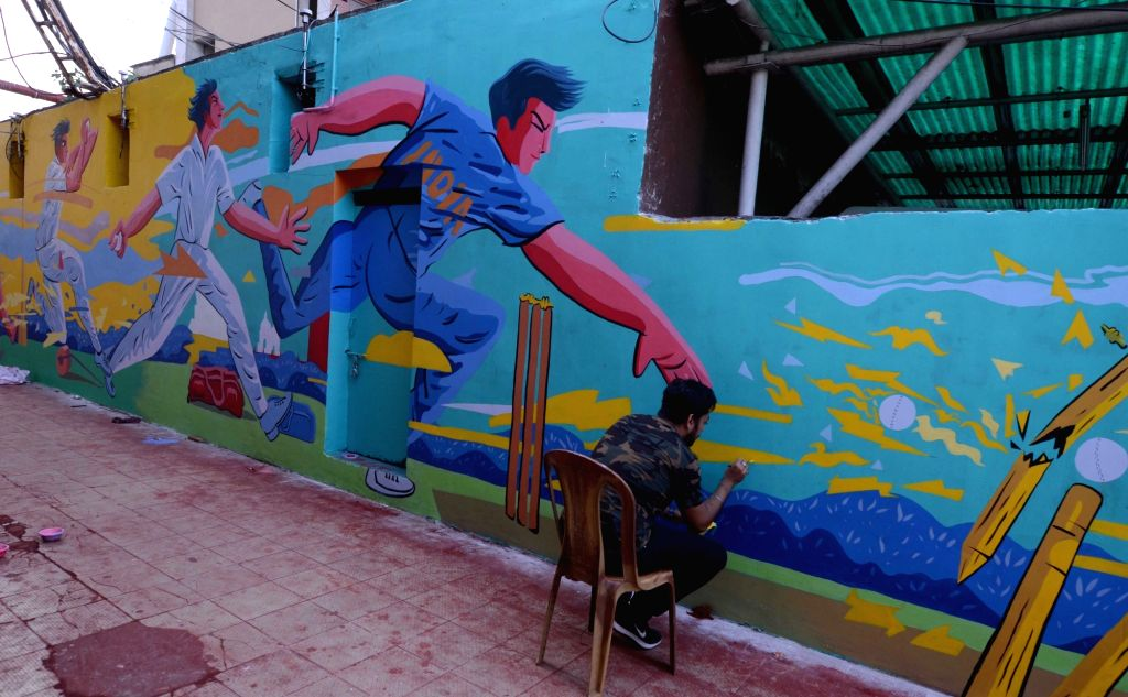 An artist paints the inside wall of Eden Gardens ahead of the first Day-Night test match between India and Bangladesh, in Kolkata on Nov. 17, 2019.